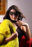 戴着性感的女用贴身内衣裤、皮大衣和面具的引诱的夫人的画象 免版税库存照片