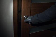 戴着手套的人在晚上打开门 免版税库存照片