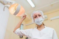 戴着手术口罩的年轻女性牙医画象,当拿着牙齿灯时 免版税库存照片