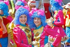 戴着明亮的服装和蓝色假发在狂欢节队伍的两个女孩城市天在伏尔加格勒 免版税库存照片