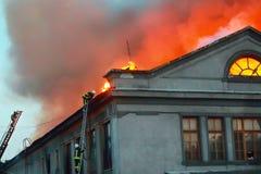着火房子的屋顶的消防队员 库存照片