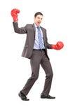戴着红色拳击手套的商人的全长画象 免版税库存照片