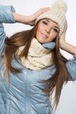 戴着羊毛米黄帽子的一名年轻深色的妇女的画象和 库存照片