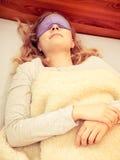戴着蒙住眼睛的睡眠面具的睡觉的妇女 库存照片