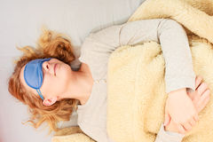 戴着蒙住眼睛的睡眠面具的睡觉的妇女 免版税库存图片