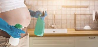 戴着蓝色手套的孕妇清洗洗手间 库存图片