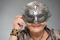 戴着迷人的面具的年长妇女 免版税库存图片