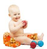 着迷的孩子拿着红色圣诞节球,欢乐箱子 库存图片
