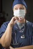 戴着防护面罩的沉思女性医生或护士 库存照片