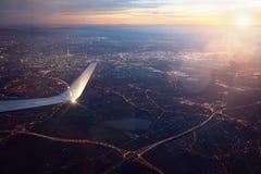 从着陆城市飞机窗口的看法日落的 免版税图库摄影