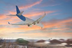 着陆飞机尾巴视图  飞行在高速公路的航空器 有高交通的路在机场跑道附近 键入O 免版税库存图片