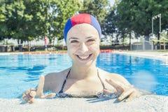 戴着水池帽子的俏丽的女孩在游泳池边飞溅wate 免版税库存图片