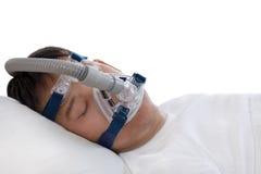 睡眠停吸疗法,睡觉在床上的人戴着CPAP面具 免版税库存照片