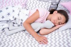 睡眠概念 小女孩睡眠在床上 与软的玩具的逗人喜爱的儿童睡眠 睡眠很好,停留健康 图库摄影