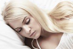 睡眠美丽的白肤金发的妇女。秀丽女孩。白色礼服。美梦 库存照片