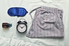 睡眠面具、安眠药、闹钟和睡衣 免版税库存照片