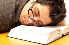 睡着的书落玻璃人年轻人 免版税库存图片