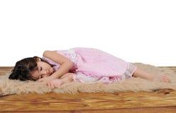 睡着的棕色毛茸的女孩少许地毯 免版税库存照片