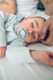 睡着的婴孩,当父母爱抚时 库存照片