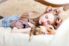 睡美人:逗人喜爱的狗和白肤金发的美丽的画报女孩有红色嘴唇卷发的人的在她的在床眼睛的头发关闭了 库存照片