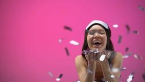 睡衣和眼罩吹的五彩纸屑的亚裔女孩,隔绝在桃红色背景 影视素材