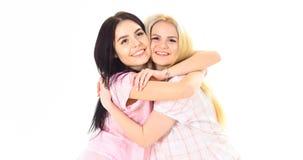睡衣拥抱的两个美丽的女孩 最好的朋友概念 微笑的面孔的夫人紧紧互相拥抱,白色 库存照片