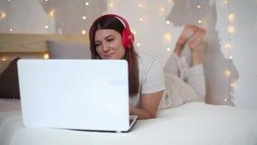 睡衣的一个美丽的性感的女孩听到在耳机的音乐的在红色使用有躺下在的一种好心情的一台膝上型计算机 股票视频