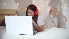 睡衣的一个美丽的性感的女孩听到在耳机的音乐的在红色使用白色颜色膝上型计算机以一种好心情 股票录像