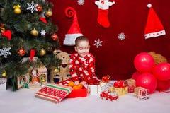 睡衣的一个逗人喜爱的婴孩对圣诞节礼物高兴 库存照片