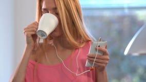 睡衣的一名愉快的妇女,跳舞在厨房里,咖啡,耳机,智能手机 影视素材
