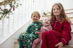 睡衣的三个孩子坐台阶在圣诞节 免版税库存照片