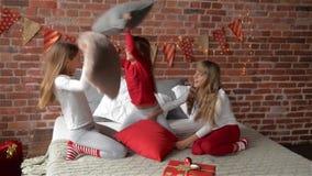 睡衣的三胞胎姐妹由枕头安排了战斗 卧室由圣诞节诗歌选和xmas装饰 股票视频