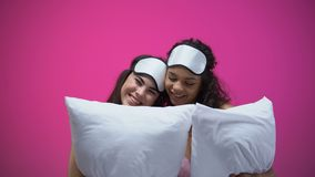 睡衣的两个夫人和笑的眼罩拿着枕头,拥抱和,休息 股票视频