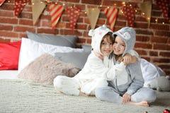 睡衣的两个孩子坐床等待的圣诞节礼物 免版税图库摄影
