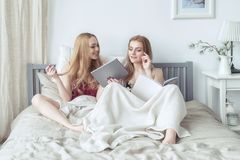 睡衣的两个性感的白肤金发的女孩获得乐趣在卧室 在床上的年轻女性使用片剂 免版税库存图片