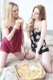 睡衣的两个愉快的女孩一起花费时间在bachelorette党和在床上的吃薄饼 图库摄影