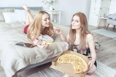 睡衣的两个愉快的女孩一起花费时间在bachelorette党和在床上的吃薄饼 免版税库存图片