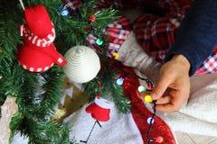 睡衣的人装饰圣诞树的户内 库存照片