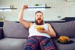 睡衣的厚实的滑稽的人吃汉堡的坐长沙发 免版税图库摄影