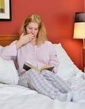 睡衣的可爱的妇女在河床上读一本水多的书的 库存图片