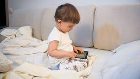 睡衣的可爱的小孩男孩观看在片剂的动画片在床上 免版税库存照片