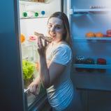 睡衣的吃薄饼的妇女画象在开放冰箱在附近 免版税库存图片