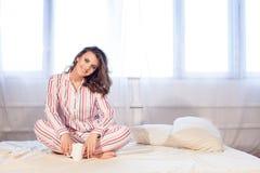 睡衣的女孩早晨醒了和饮料咖啡或者茶 免版税库存照片