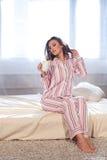 睡衣的女孩早晨醒了和饮料咖啡或者茶 库存照片