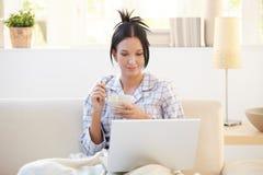 睡衣的女孩饮用谷物使用膝上型计算机 免版税库存图片