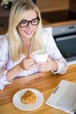 睡衣的妇女喝咖啡和在家使用膝上型计算机的 免版税库存照片