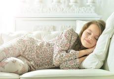 睡衣的小女孩睡觉在长沙发的 免版税库存照片