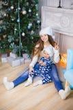 睡衣的小男孩和圣诞老人帽子在圣诞树附近坐与他的姐妹的微笑 显示和平 免版税库存图片