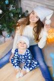 睡衣的小男孩和圣诞老人帽子在圣诞树附近坐与他的姐妹的微笑 免版税库存照片