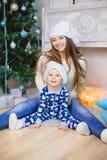 睡衣的小男孩和圣诞老人帽子在圣诞树附近坐与他的姐妹的微笑 库存图片